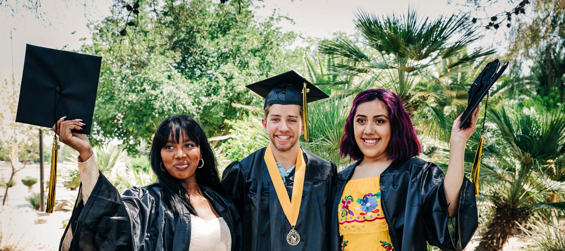 Three happy graduates from Nevada State High School Home Page Header